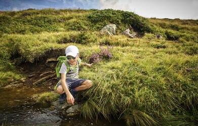 Boy crouching at a mountain stream, Passeier Valley, South Tyrol, Italy - DIKF00330