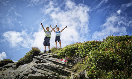 Boy and girl standing on mountaintop cheering, Passeier Valley, South Tyrol, Italy - DIKF00336