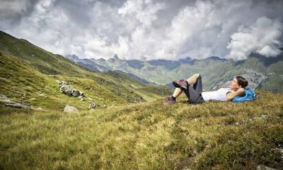 Woman having a break from hiking lying on alpine meadow, Passeier Valley, South Tyrol, Italy - DIKF00339