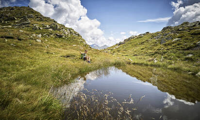 Boy having a break from hiking sitting at a mountain lake, Passeier Valley, South Tyrol, Italy - DIKF00342