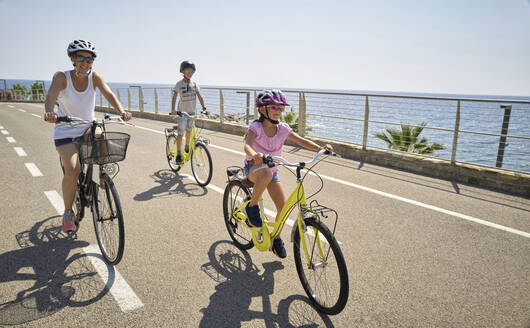 Mother with children during bicycle tour between San Lorenzo and San Remo, Italy - DIKF00350