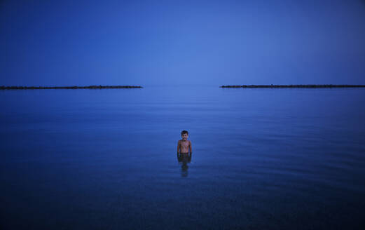 Boy bathing in the sea at night, Italy - DIKF00353