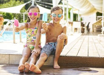 Portrait of happy little girl and boy wearing mirrored sunglasses showing their popsicles - DIKF00359