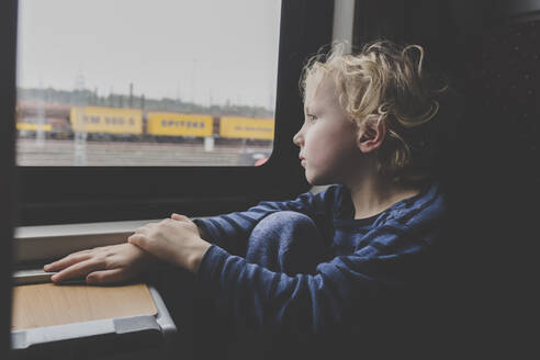Little boy sitting in train looking out of window - IHF00221