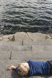 Little boy resting at lakeshore - IHF00230