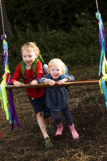 Portrait of boy and his little sister having fun with a swing - IHF00233