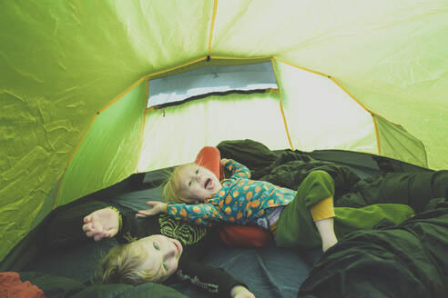 Siblings playing together in a tent - IHF00239
