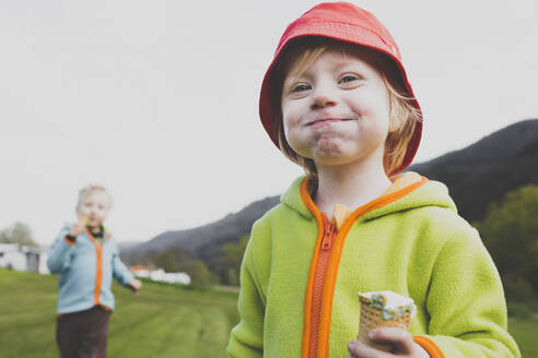 Portrait of little girl eating ice cream outdoors - IHF00242