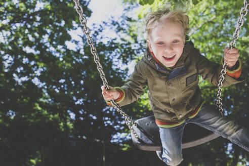 Portrait of happy little boy on a swing - IHF00251