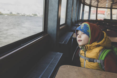 Portrait of little boy looking out of window of a ferry - IHF00254