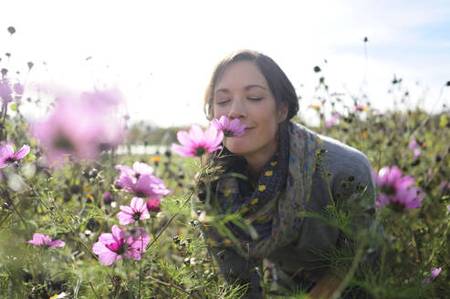 Portrait of women smelling on wild flower, flower meadow - ECPF00789