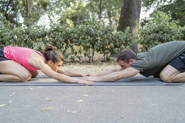 Man and woman stretching on a gym mat outdoors - FBAF01101