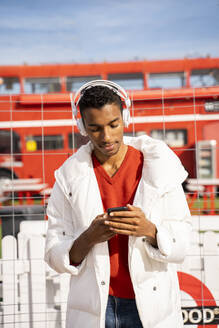 Young man headphones and smartphone outdoors - AFVF04653