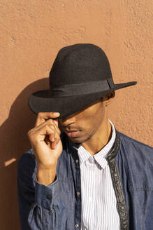 Stylish young man wearing a hat at a wall - AFVF04683