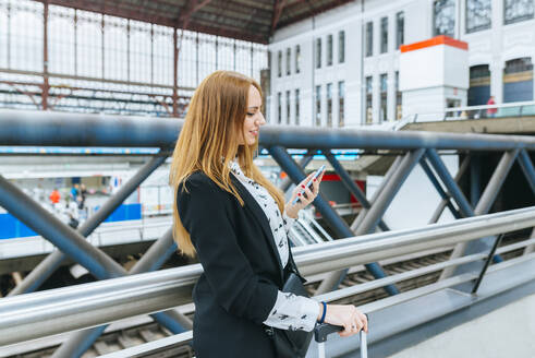 Young woman using cell phone at train station - KIJF02858