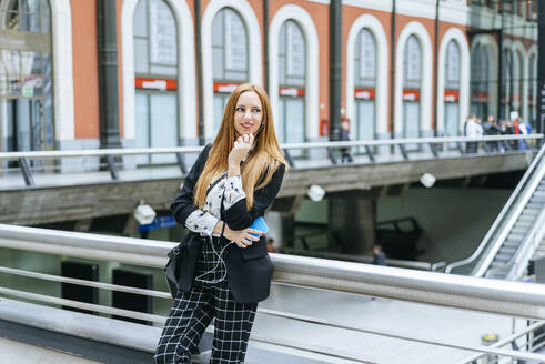 Young woman with earphones and cell phone at train station - KIJF02867