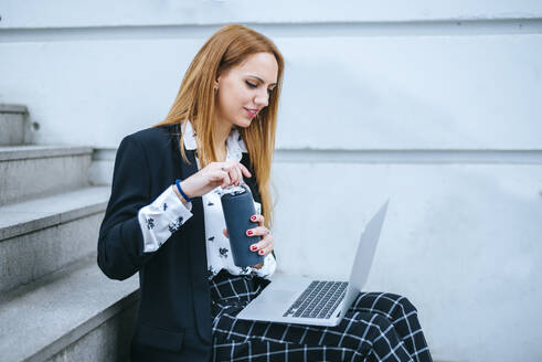 Young businesswoman sitting on stairs with laptop and reusable bottle - KIJF02873