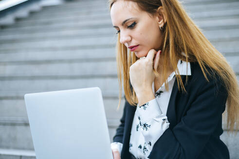 Young businesswoman sitting on stairs using laptop - KIJF02876