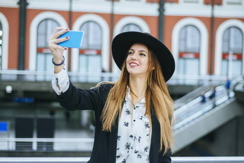 Smiling young woman wearing a hat taking a selfie at train station - KIJF02885