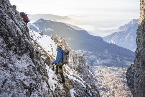 Alpinist standing in a rocky snowy mountain looking up, Orobie Alps, Lecco, Italy - MCVF00146