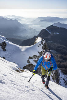 Alpinist ascending a snowy mountain, Orobie Alps, Lecco, Italy - MCVF00152