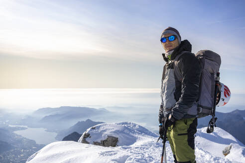 Portrait of an alpinist standing on snowy mountain peak, Orobie Alps, Lecco, Italy - MCVF00155
