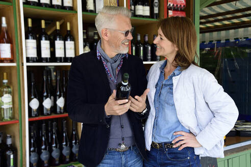 Mature couple choosing bottle of wine at a wine shop - ECPF00840