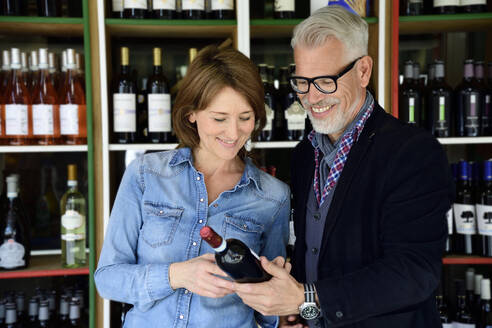 Mature couple choosing bottle of wine at a wine shop - ECPF00846