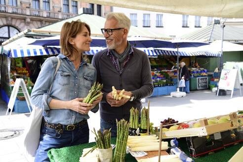 Mature couple choosing asparagus at a market stall - ECPF00852