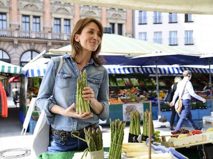 Mature woman choosing asparagus at a market stall - ECPF00855