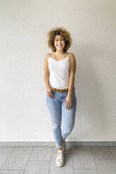 Smiling mid adult woman wearing jeans - FMKF06059