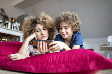 Mother and son watching a video on smartphone, lying on big pillow - FMKF06068