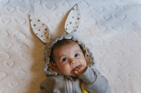 Portrait of baby girl in a rabbit hoodie with finger in mouth lying on white blanket - GEMF03379