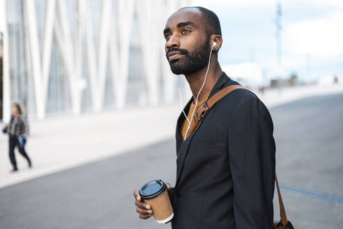 Portrait of young businessman with coffee to go listening music with earphones outdoors - JSRF00695