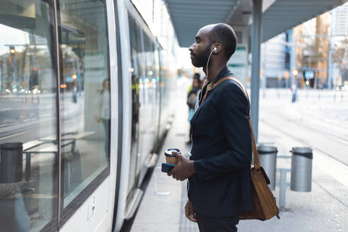 Young businessman with coffee to go standing at tram stop listening music with earphones and smartphone - JSRF00704