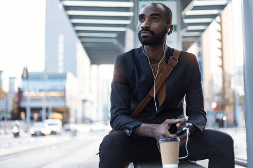 Portrait of young businessman  listening music with earphones and smartphone at tram stop - JSRF00707