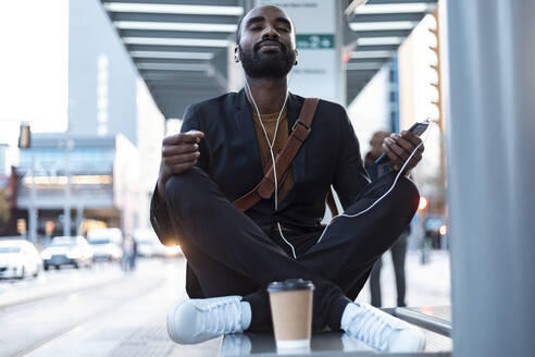 Portrait of young businessman with earphones and smartphone meditating on bench at tram stop - JSRF00710