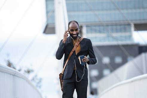 Smiling young businessman using smartphone and earphones outdoors - JSRF00716