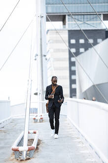 Young businessman with earphones and coffee to go walking on footbridge while looking at smartphone - JSRF00725