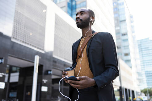 Young businessman with coffee to go listening music with earphones and smartphone in the city - JSRF00728