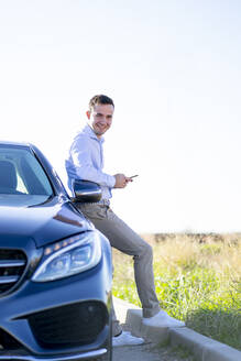 Portrait of smiling young businessman leaning against car on country road holding smartphone - CJMF00217