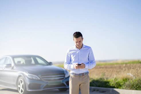 Young businessman with car on country road using smartphone - CJMF00223