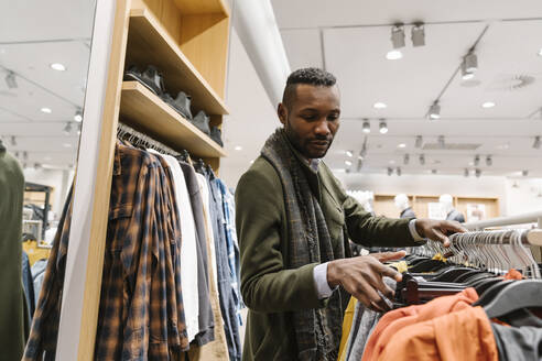 Stylish man shopping in a clothes store - AHSF01640