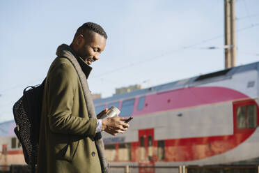 Stylish man with reusable cup using smartphone while waiting for the train - AHSF01679