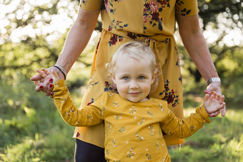 Portrait of little blond girl hand in hand with her mother on a meadow - NMSF00399