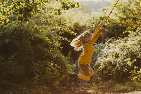 Happy little girl swinging on a rope swing in nature - NMSF00402