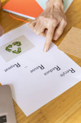 Businesswoman pointing on paper with recycling symbol in office - AFVF04741