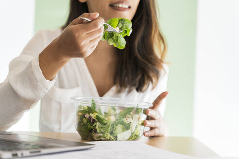 Crop view of young architect eating mixed salad at desk - AFVF04771