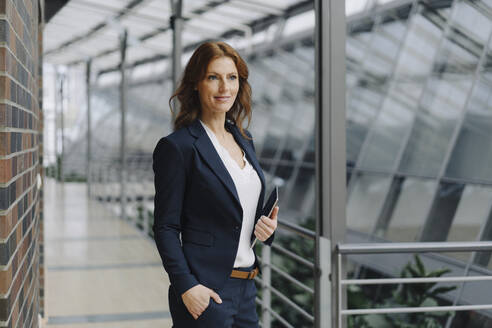 Confident businesswoman holding a tablet in a modern office building - JOSF04149