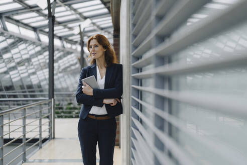 Confident businesswoman holding a tablet in a modern office building - JOSF04152
